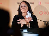 Tantoo Cardinal, recipient of the Technicolor Clyde Gilmour prize, speaking at the TFCA podium.